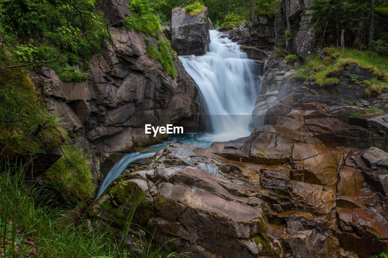 water, waterfall, long exposure, rock, scenics - nature, flowing water, motion, rock - object, beauty in nature, forest, land, solid, blurred motion, power in nature, power, nature, plant, flowing, no people, outdoors, rainforest, falling water