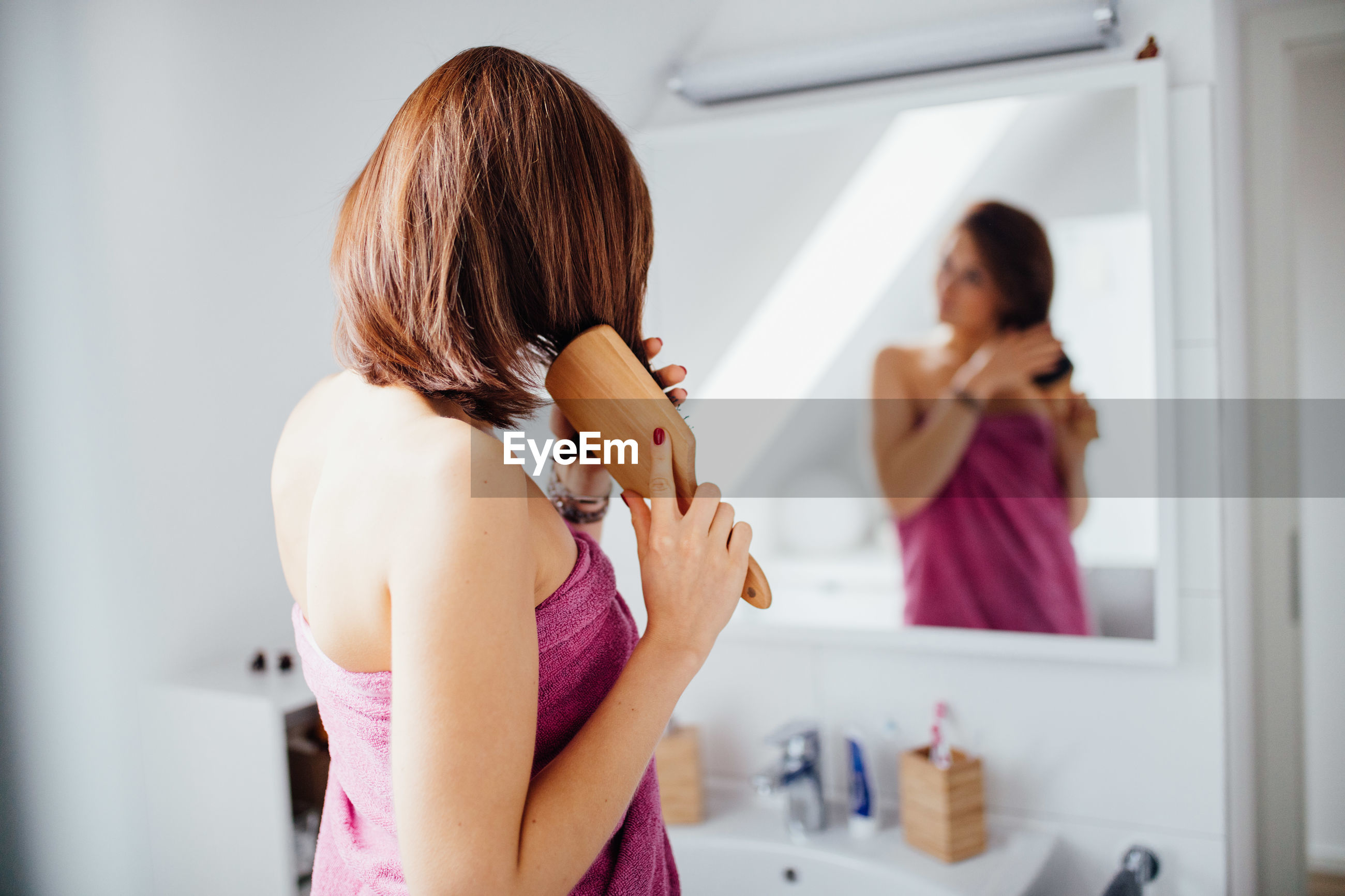 Reflection of woman combing hair in mirror