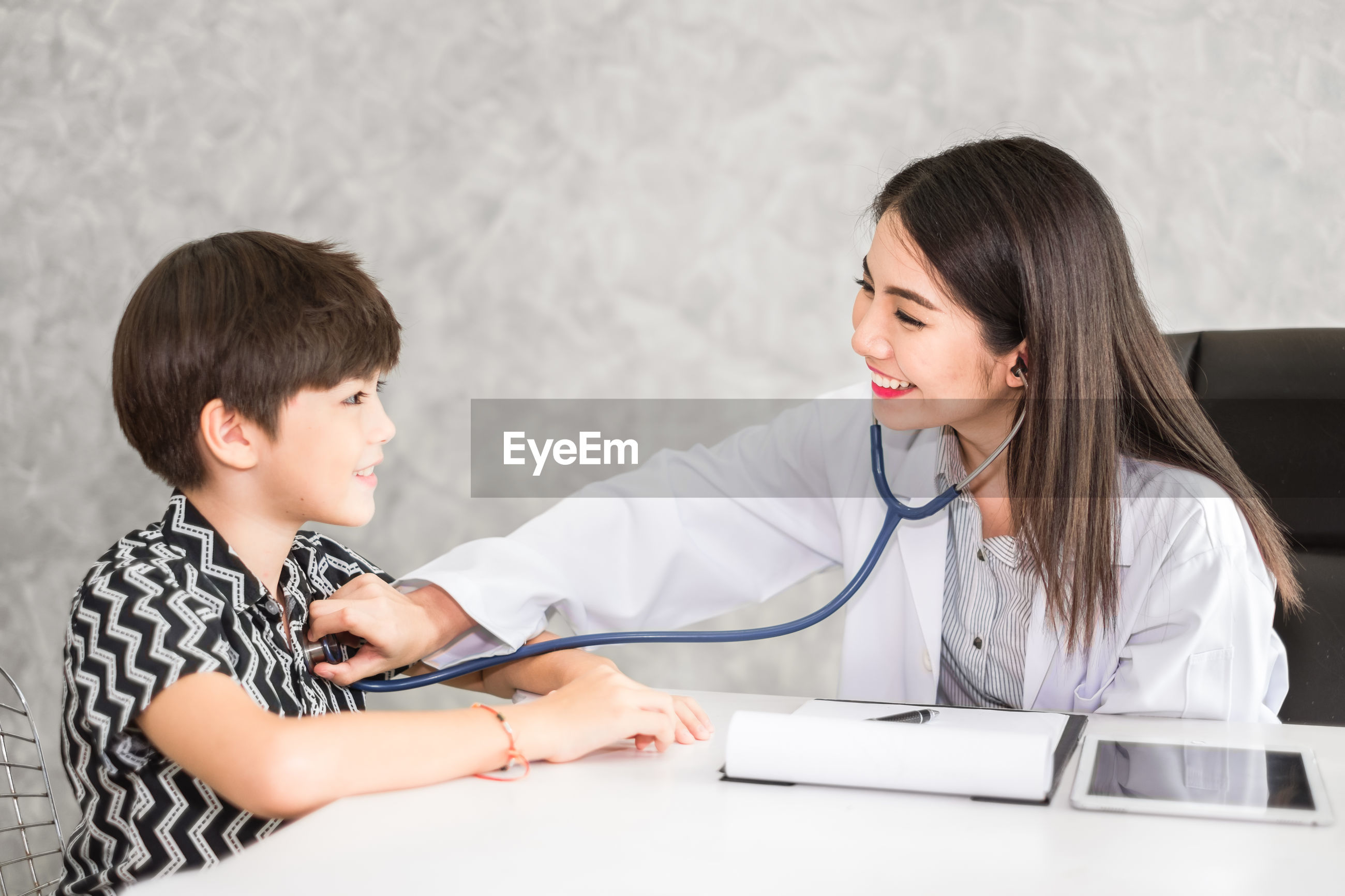 Smiling female doctor examining boy at clinic