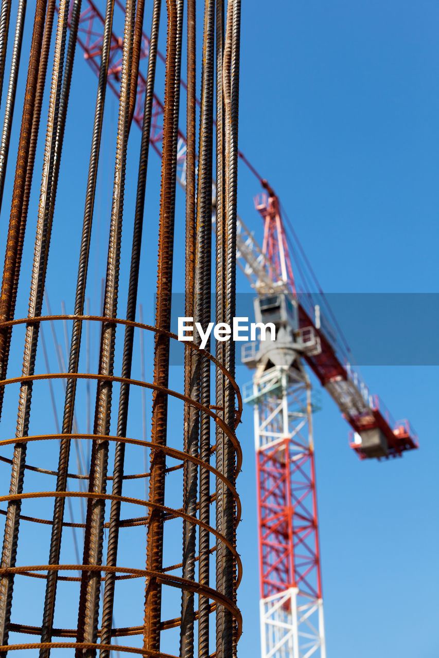 low angle view, construction site, blue, day, built structure, clear sky, no people, architecture, arts culture and entertainment, amusement park, outdoors, sunlight, sky, technology