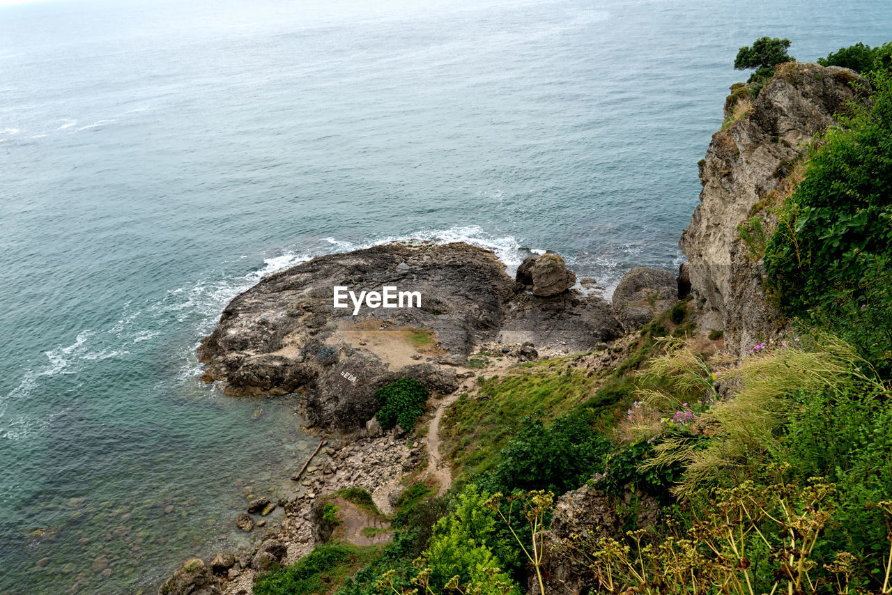 sea, water, beauty in nature, rock, tranquility, scenics - nature, high angle view, rock - object, day, land, no people, tranquil scene, nature, rock formation, solid, beach, plant, outdoors, idyllic, rocky coastline