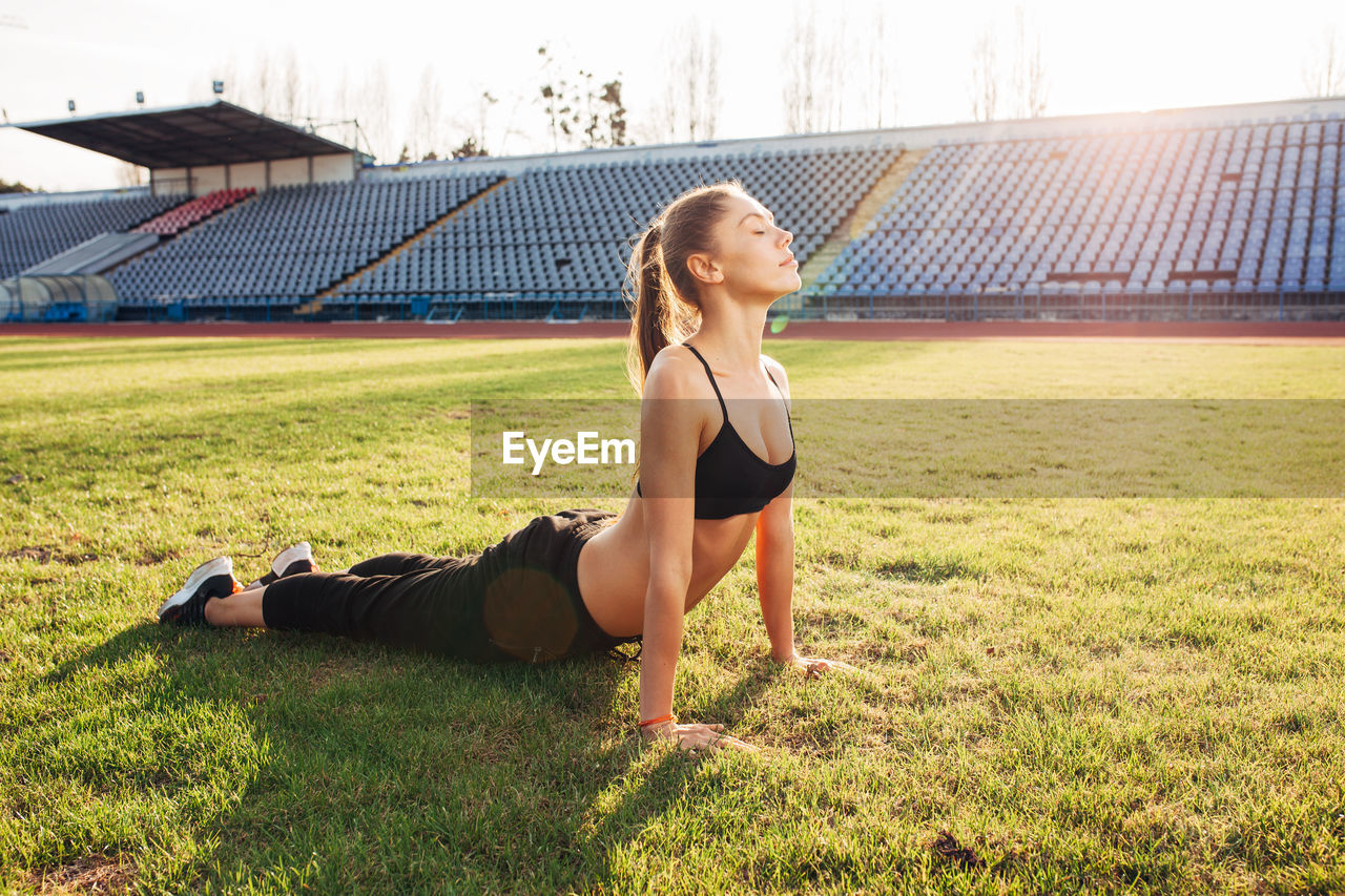 grass, one person, sport, plant, lifestyles, real people, nature, day, field, young adult, full length, leisure activity, clothing, land, young women, relaxation, sports clothing, sunlight, outdoors, hairstyle, beautiful woman