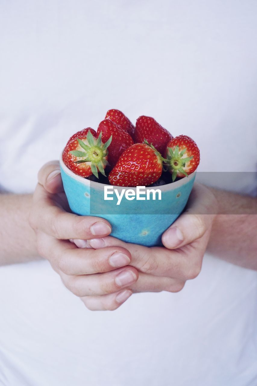 Midsection Of Man Holding Strawberries In Bowl