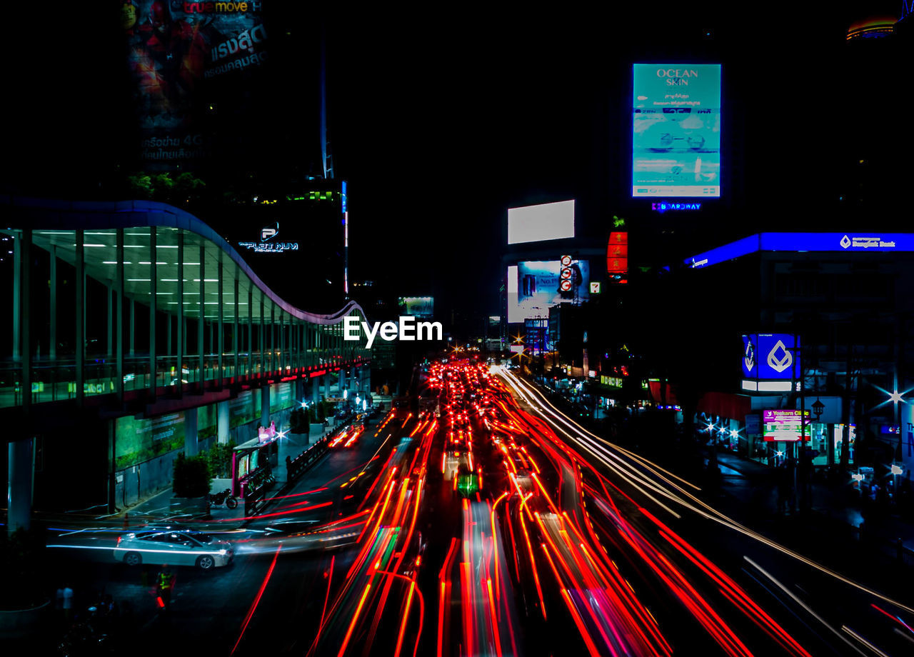 illuminated, city, motion, night, long exposure, road, architecture, light trail, speed, street, transportation, city life, building exterior, built structure, blurred motion, traffic, mode of transportation, city street, no people, outdoors