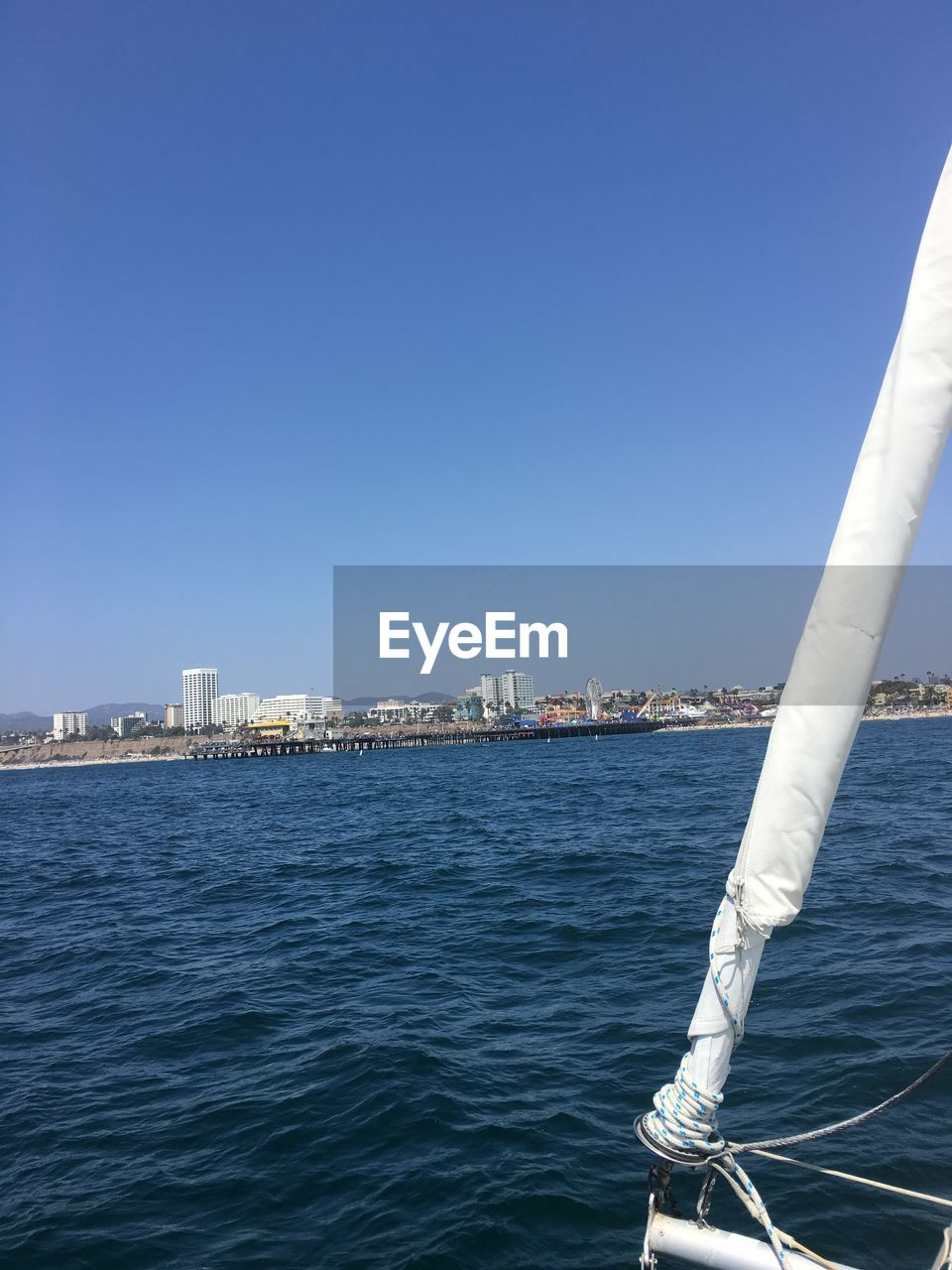 copy space, water, sea, nautical vessel, mode of transport, day, blue, transportation, clear sky, outdoors, built structure, no people, architecture, sailing, nature, city, wake, sky, cityscape