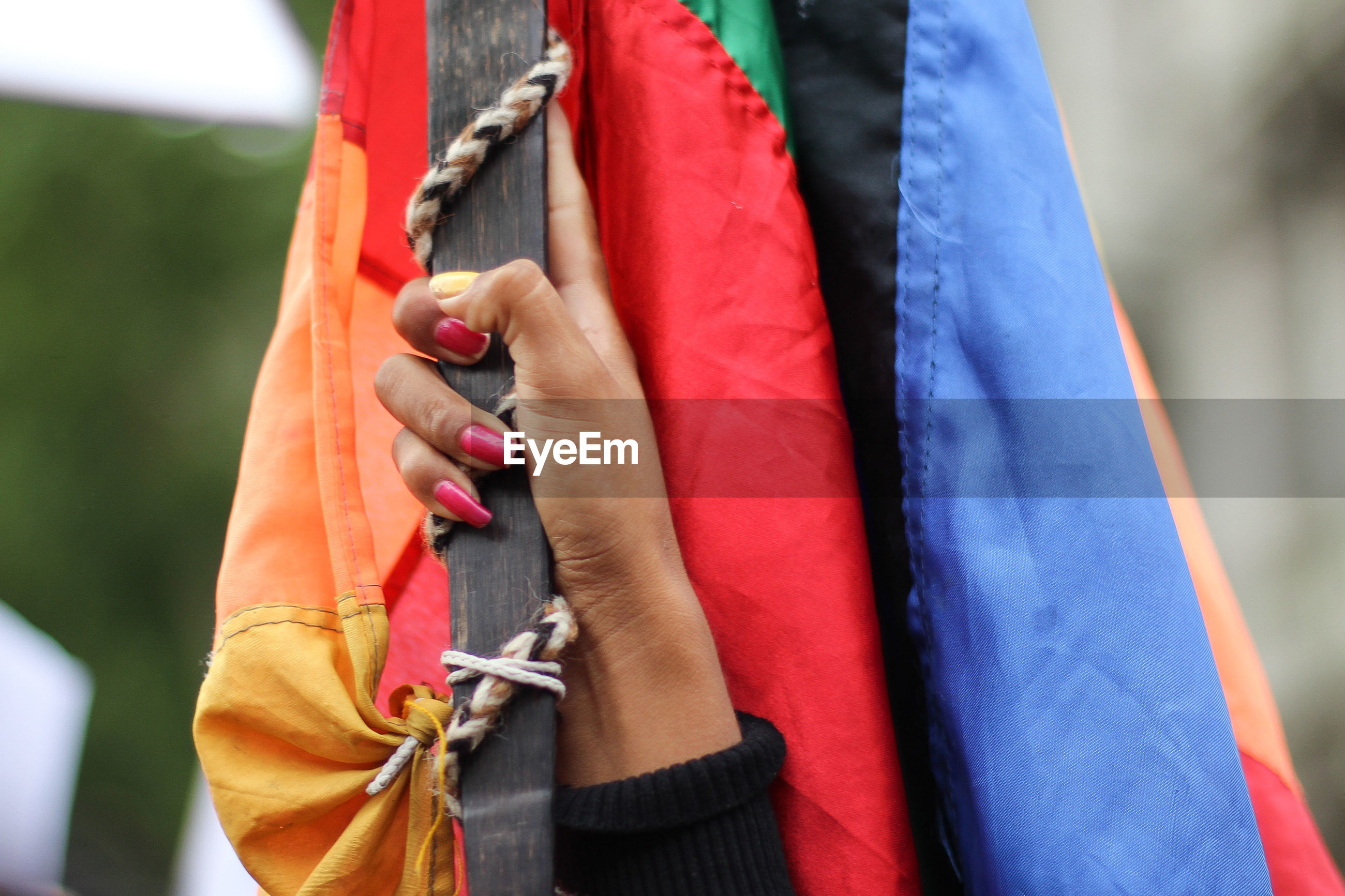 Cropped hand holding colorful flag