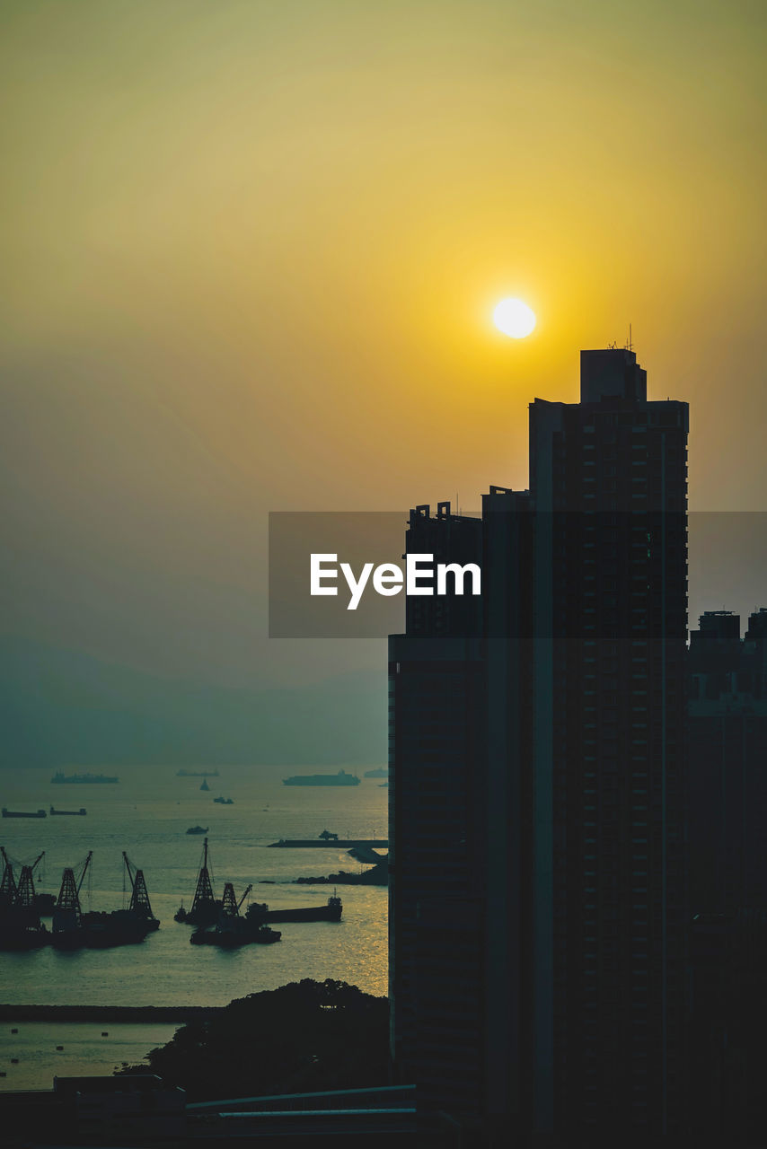 sky, sunset, architecture, water, built structure, building exterior, city, orange color, nature, sea, sun, silhouette, building, office building exterior, no people, skyscraper, scenics - nature, cityscape, beauty in nature, outdoors