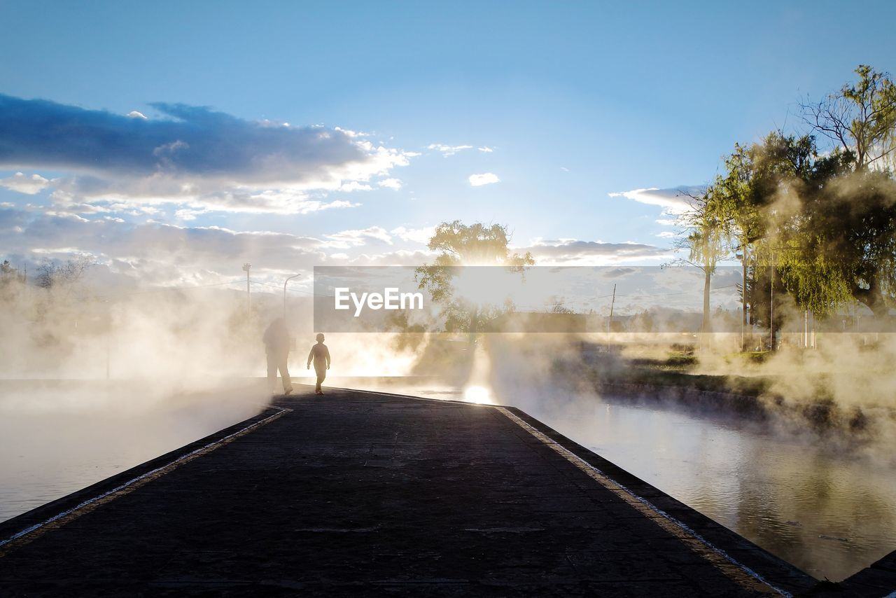 sky, nature, tree, beauty in nature, water, scenics - nature, day, the way forward, men, real people, direction, standing, steam, plant, fog, lifestyles, tranquil scene, sunlight, full length, outdoors, hot spring, power in nature