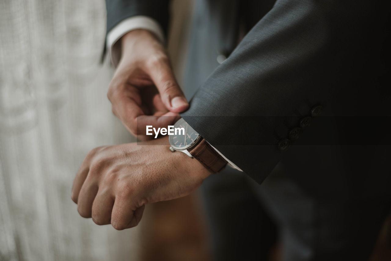 Midsection Of Businessman Adjusting Sleeve