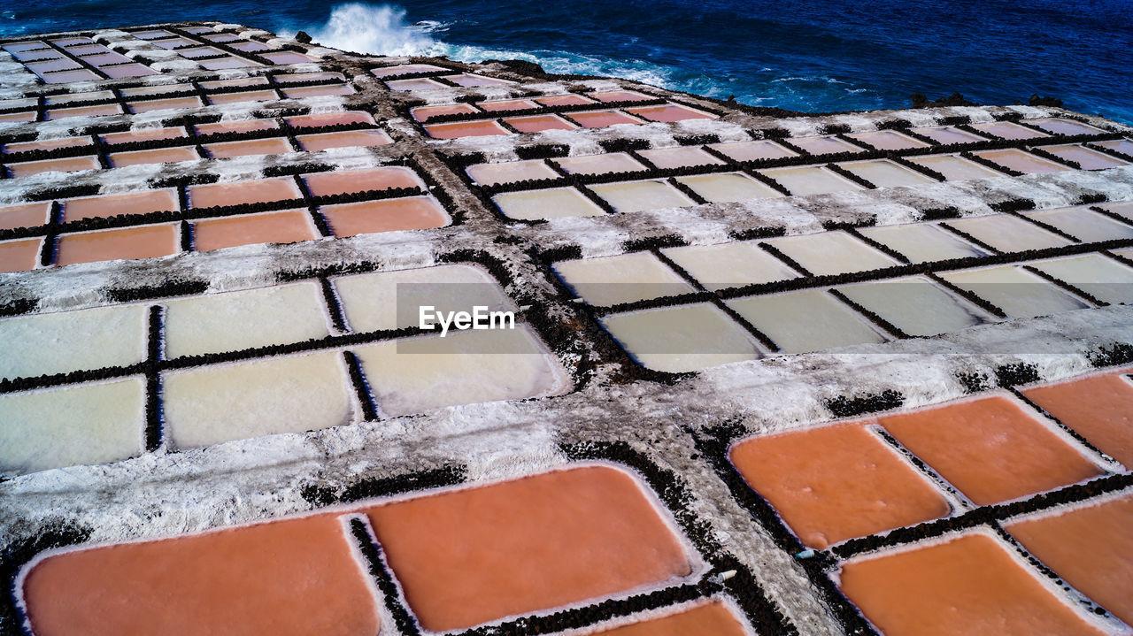 High angle view of salt flat sea salk farm water fields multicolour texture background
