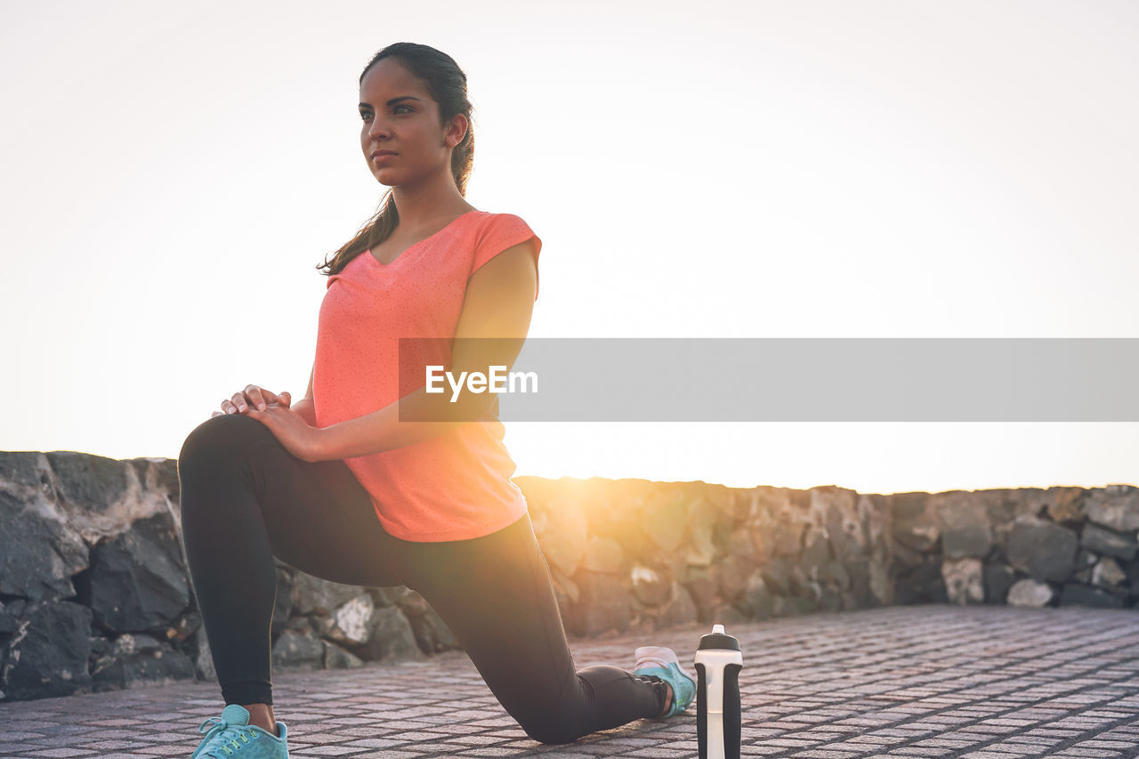 Young woman exercising on promenade against sky during sunset