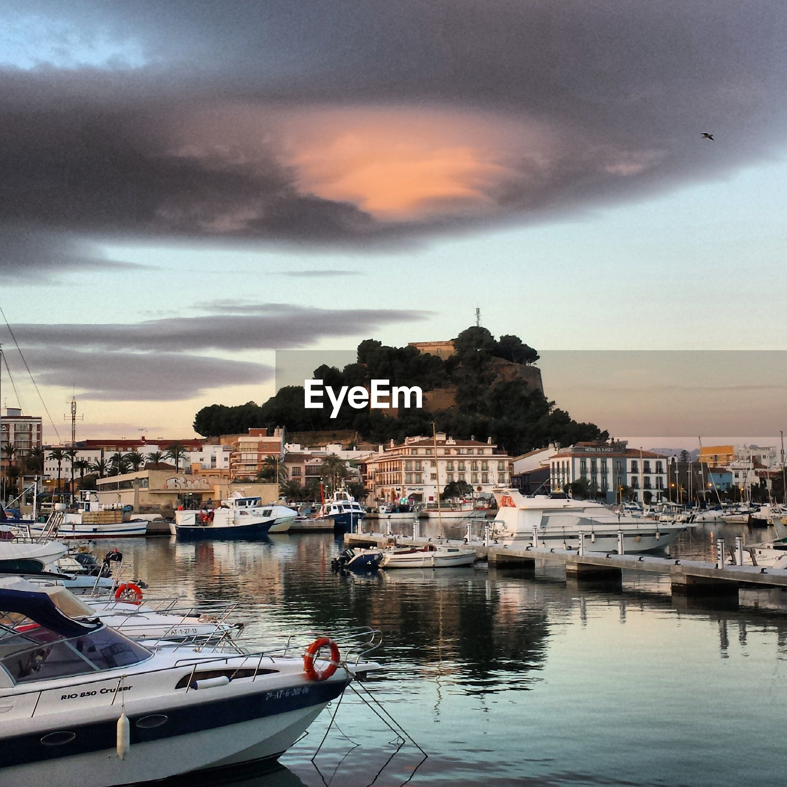 nautical vessel, moored, transportation, water, mode of transport, sky, boat, building exterior, architecture, built structure, sea, harbor, cloud - sky, sunset, cloudy, waterfront, cloud, town, house, mountain