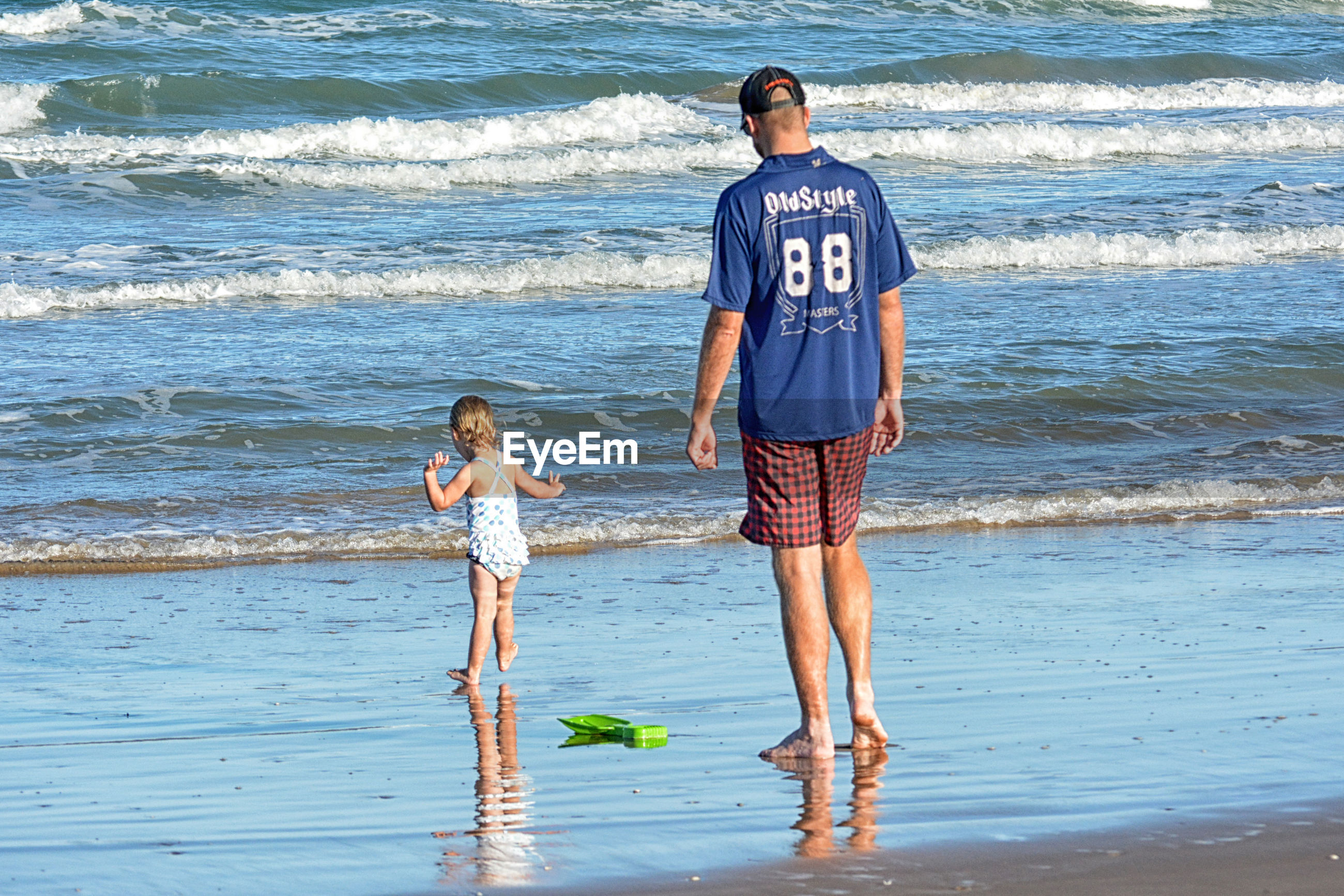 Rear view of father with daughter standing on shore at beach during sunny day