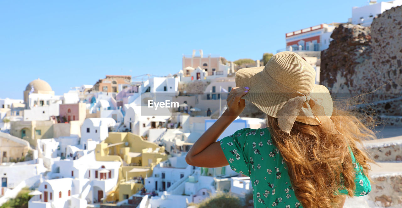 hat, real people, architecture, building exterior, one person, built structure, sky, leisure activity, clothing, nature, lifestyles, women, city, day, sunlight, building, adult, clear sky, rear view, hair, sun hat, hairstyle, outdoors