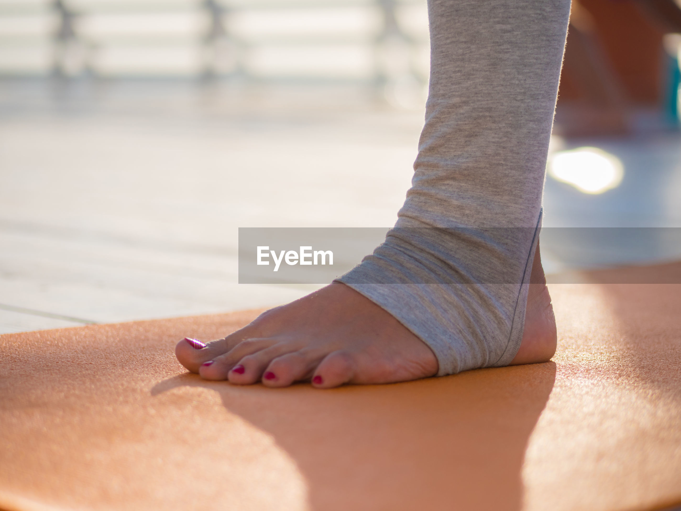 Low section of woman standing on exercise mat