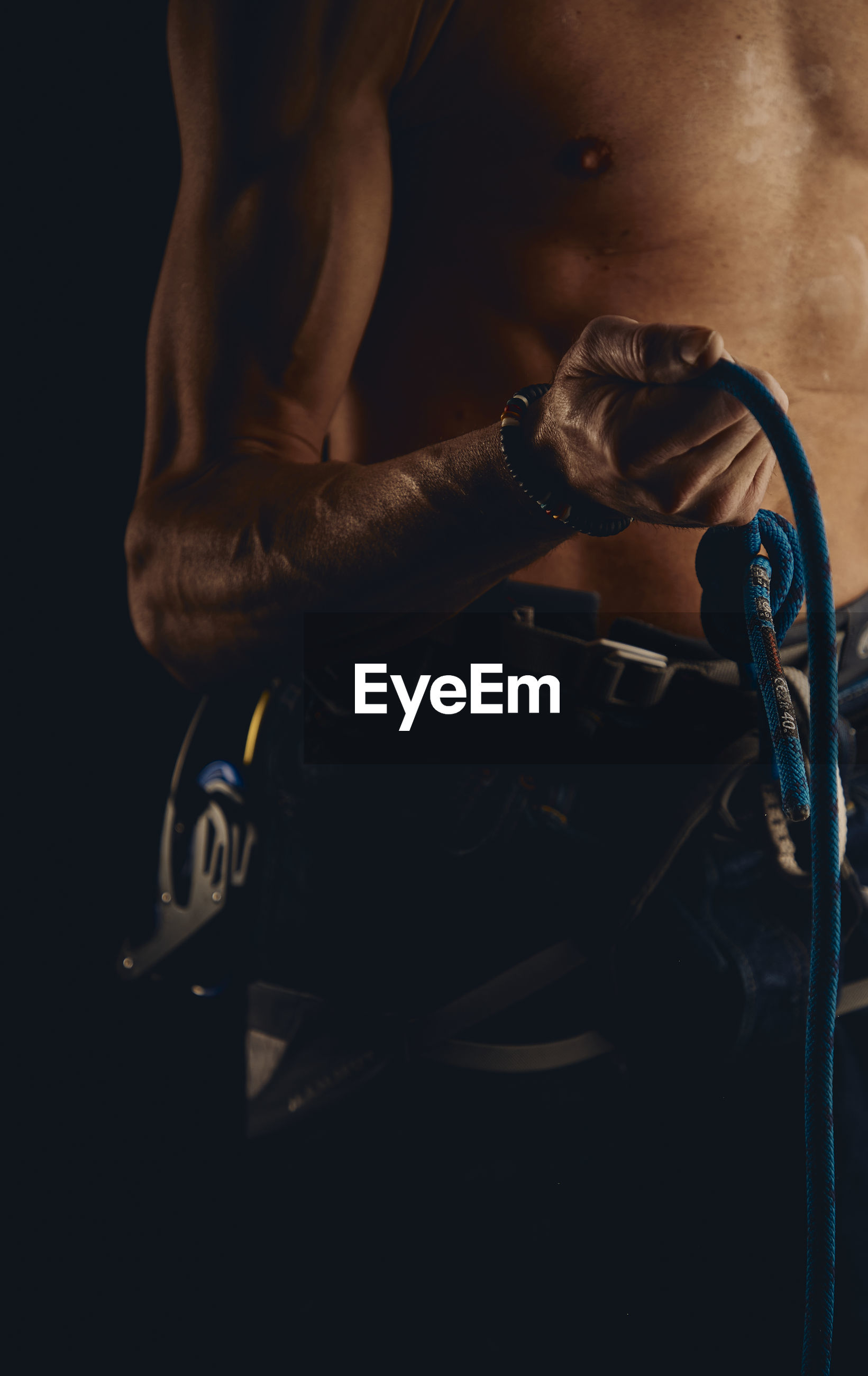 Midsection of shirtless man holding rope