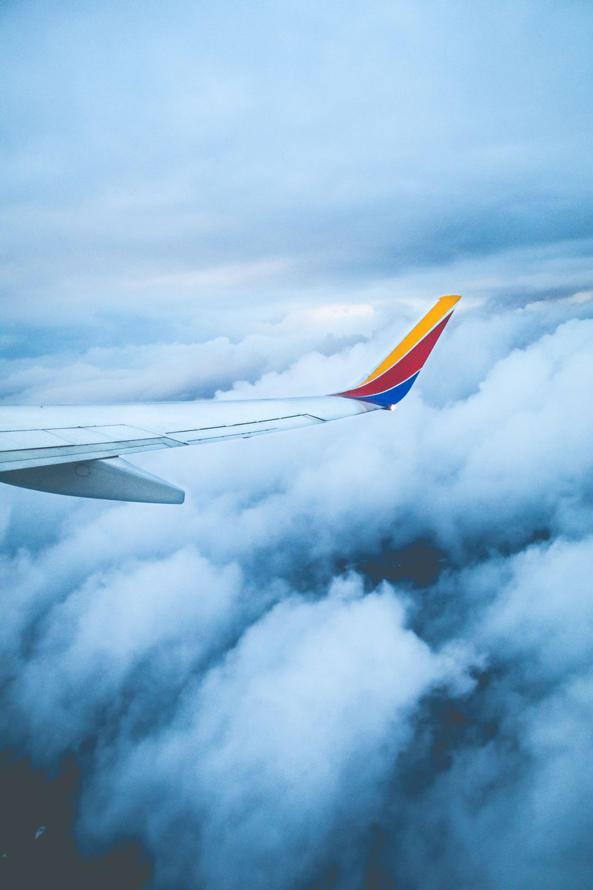 cloud - sky, flying, sky, airplane, mid-air, air vehicle, no people, nature, mode of transportation, day, low angle view, motion, transportation, outdoors, environment, multi colored, beauty in nature, aircraft wing, flag, on the move, wind, independence