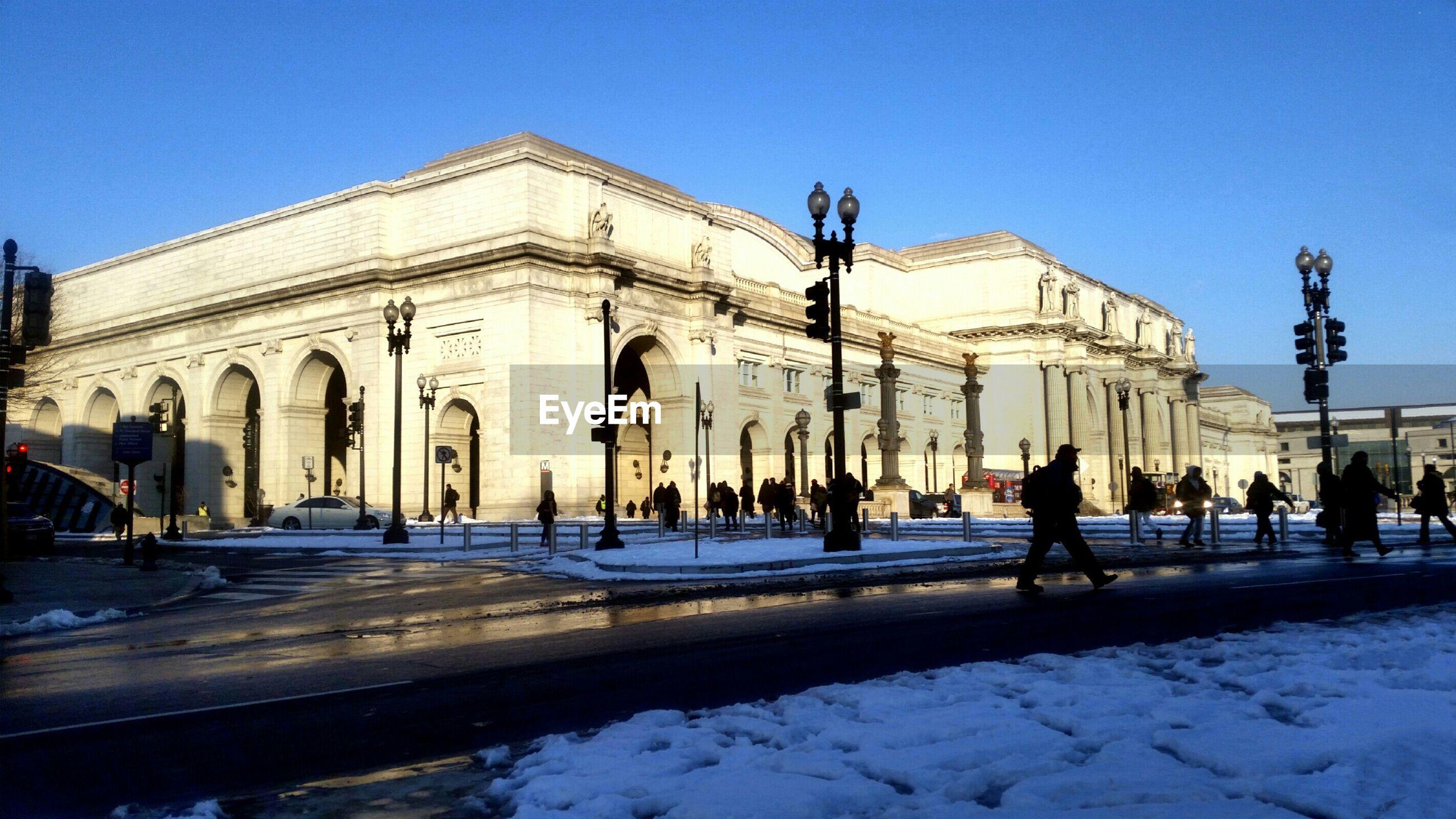 People walking on road along buildings in winter