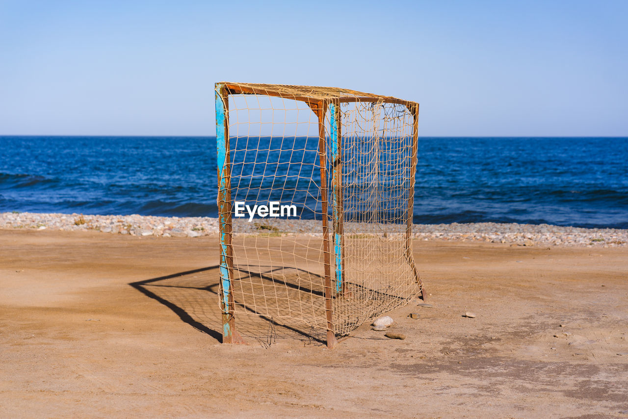 beach, land, horizon, sea, horizon over water, sky, sand, water, nature, sport, tranquility, beauty in nature, scenics - nature, day, no people, blue, absence, clear sky, net - sports equipment, outdoors