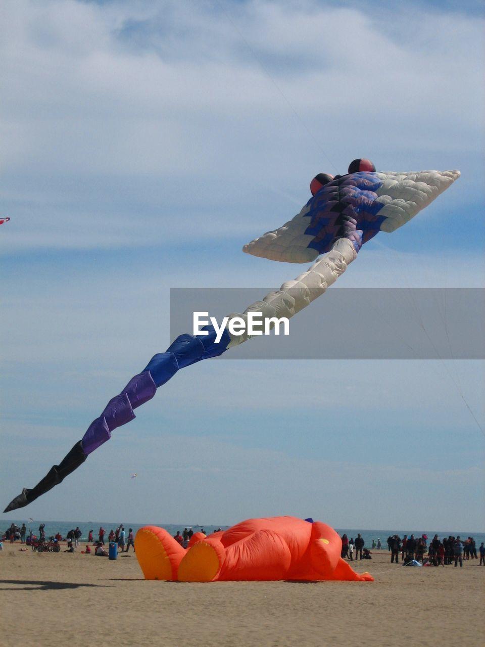 Large Kites Flying Over Beach Against Sky