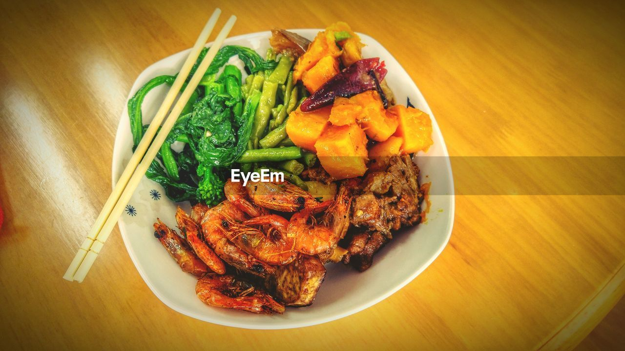 High Angle View Of Food In Plate On Wooden Table