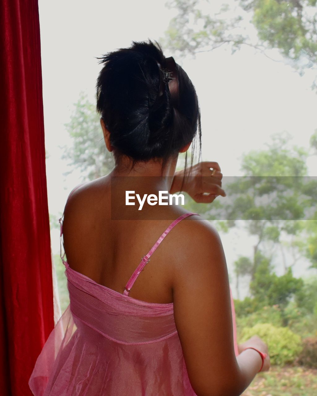 rear view, real people, one person, lifestyles, standing, focus on foreground, day, women, leisure activity, waist up, young adult, hairstyle, hair, adult, nature, young women, hair bun, window, plant, off shoulder, contemplation