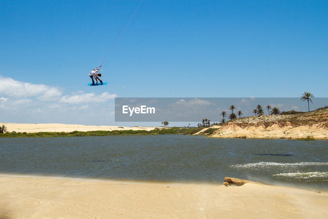 Man Kiteboarding In Sea Against Blue Sky