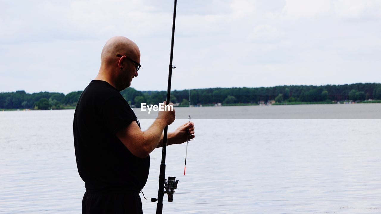 Bald Man Fishing In Lake Against Sky