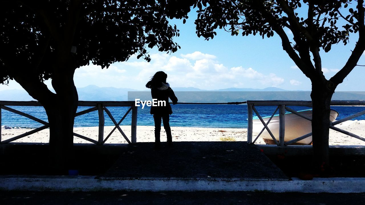 Rear View Of Silhouette Woman Standing At Beach Against Sky