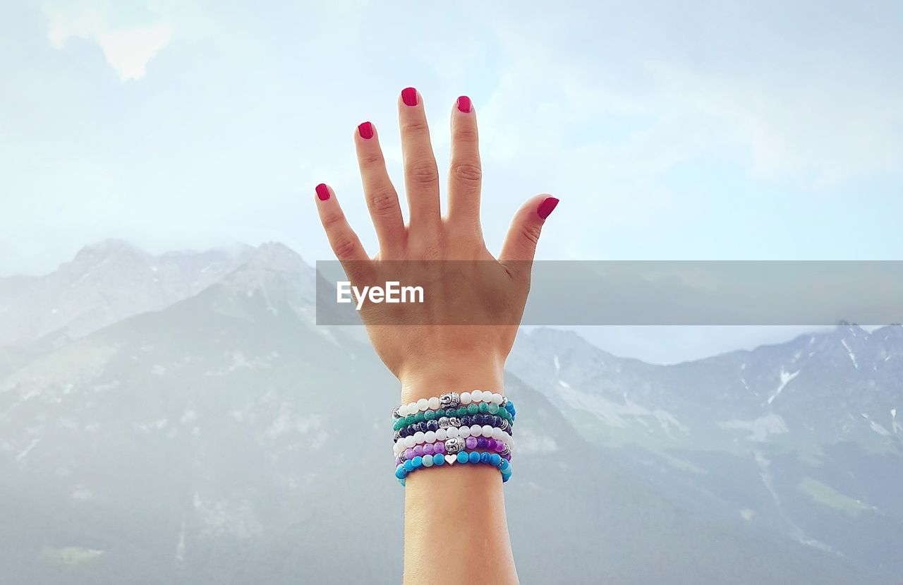 Hand Of Woman Against Sky