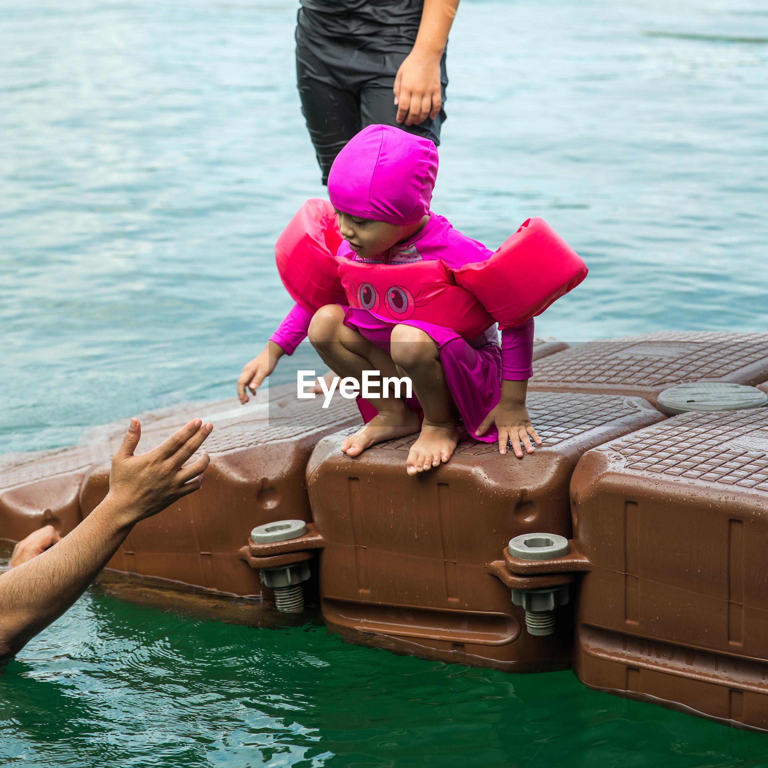 Full length of woman floating on lake