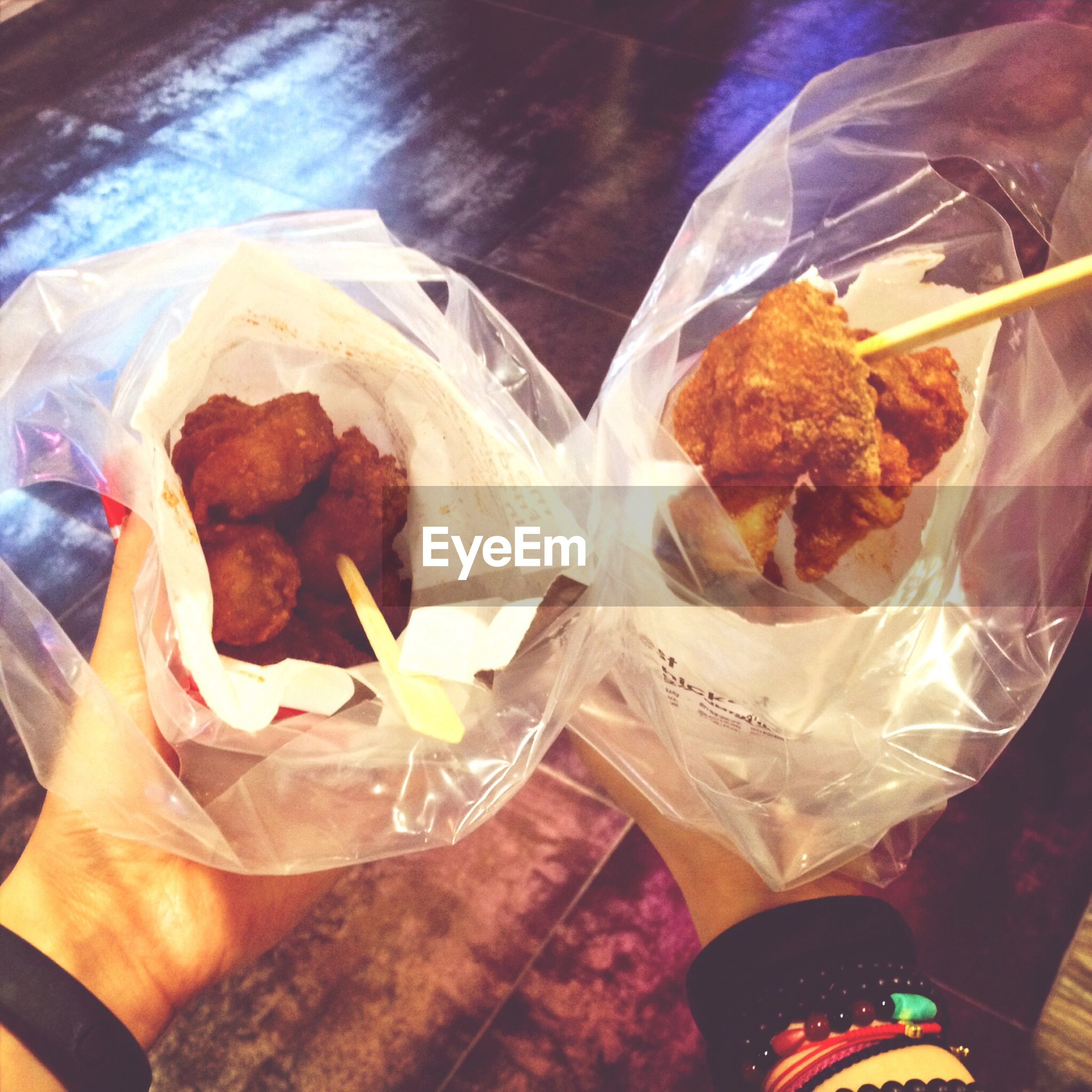 Cropped image of hands holding food in plastic bag
