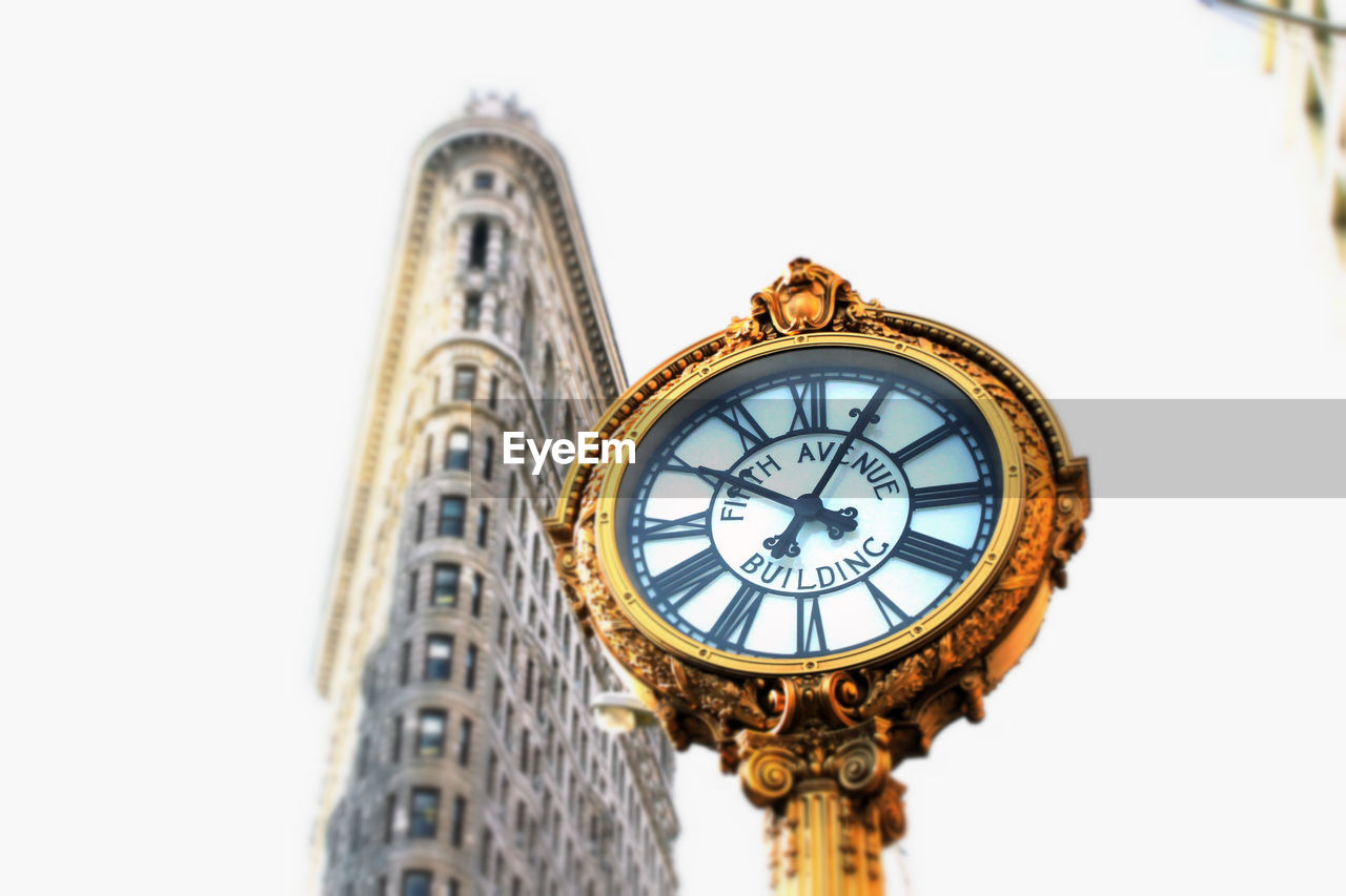 Low angle view of clock and flatiron building against sky