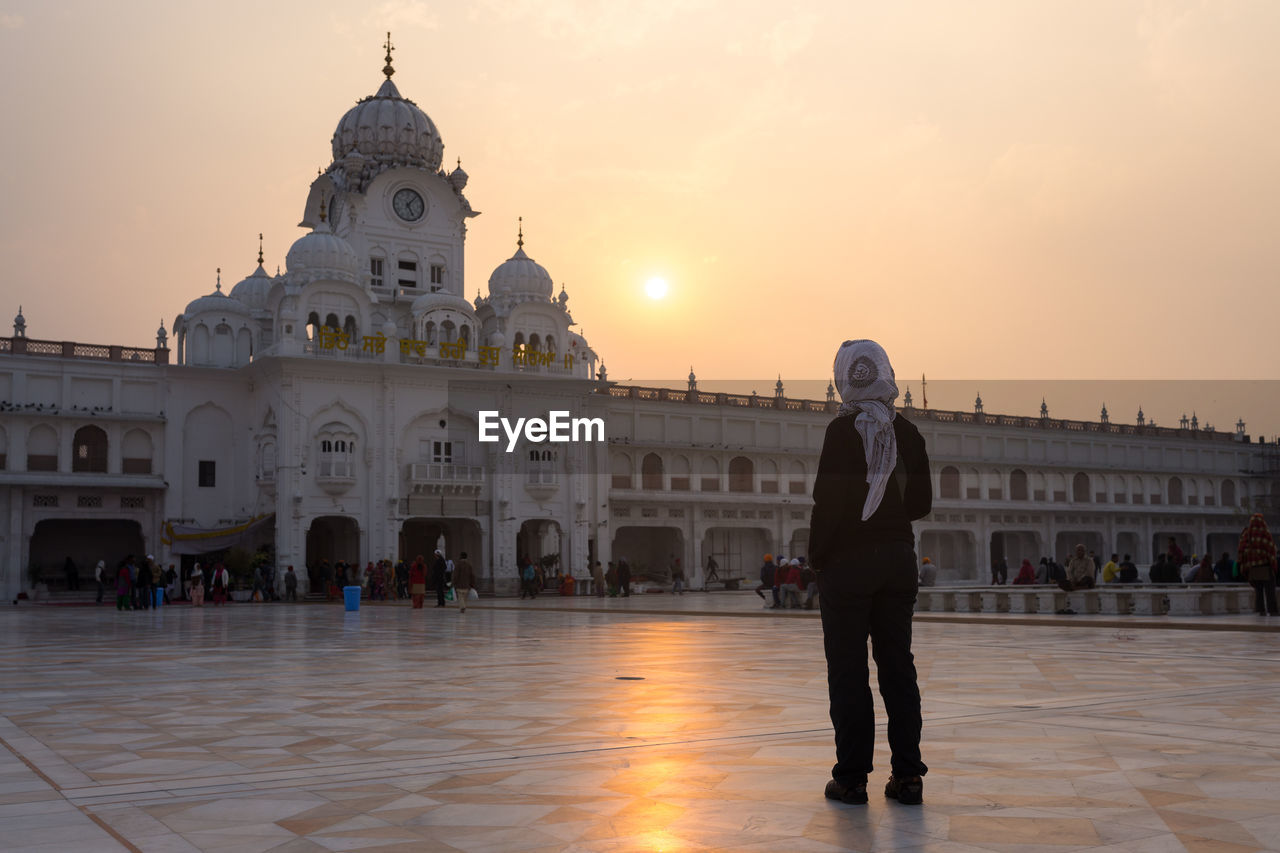 Rear view of woman standing in front of temple during sunset
