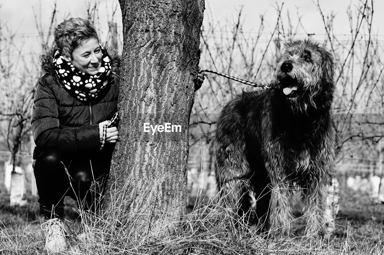 Happy Woman Playing With Irish Wolfhound By Tree At Forest