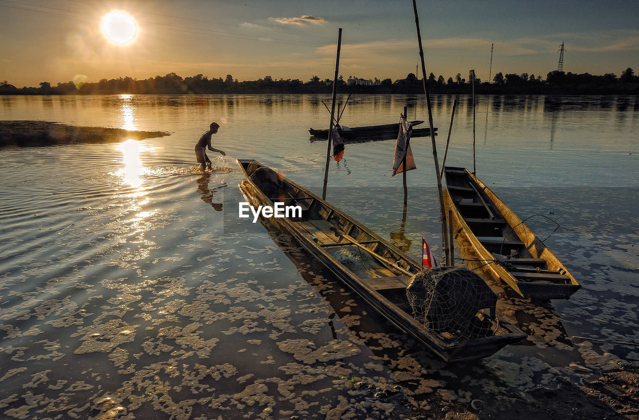 Man Fishing By Boats In Lake Against Sky During Sunset