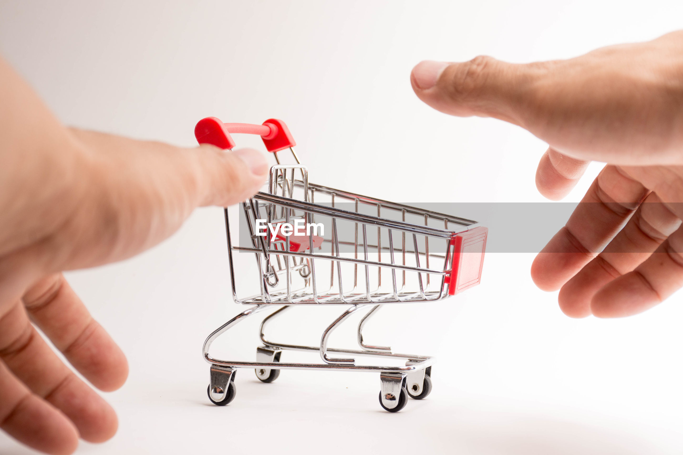 Cropped hands by toy shopping cart on white background