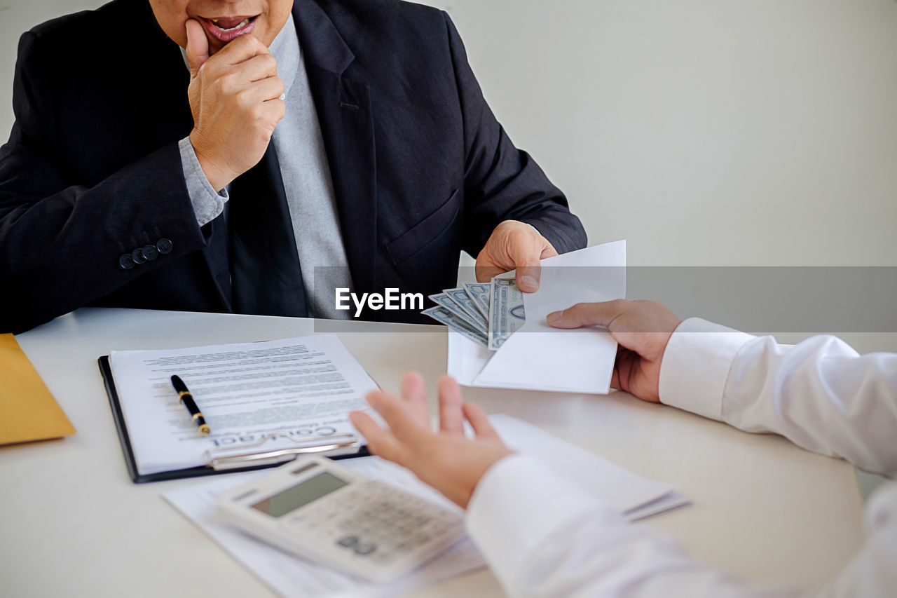 Cropped hands of man giving money in envelope to businessman