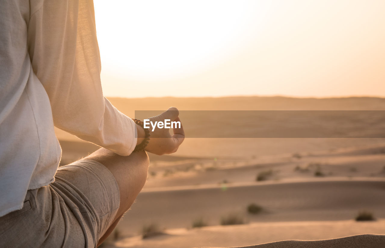 Close-Up Of Woman Meditating In Desert