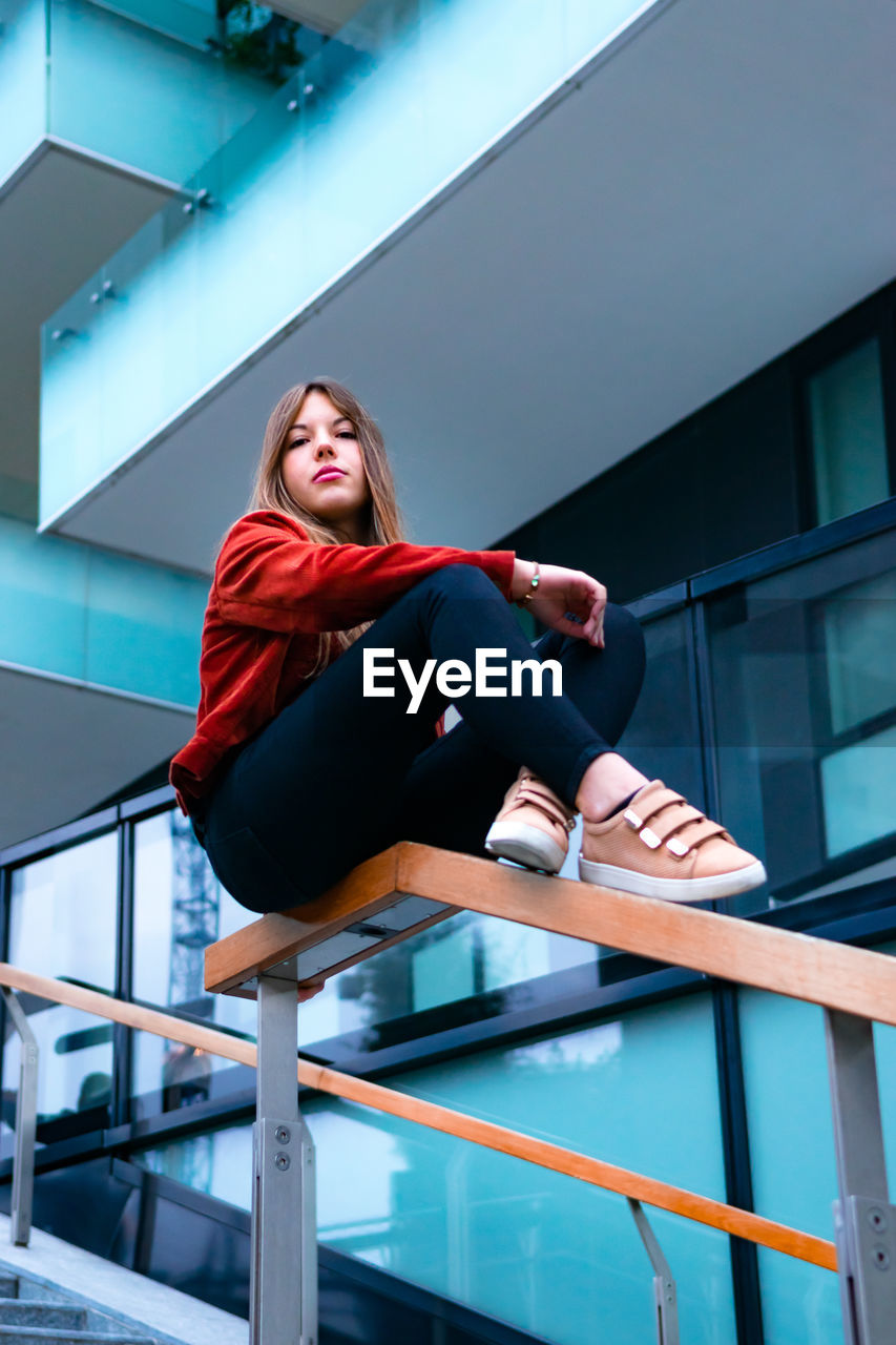 one person, real people, low angle view, lifestyles, young adult, leisure activity, full length, architecture, young women, built structure, railing, women, casual clothing, day, sitting, looking away, beauty, staircase, outdoors, beautiful woman, hairstyle