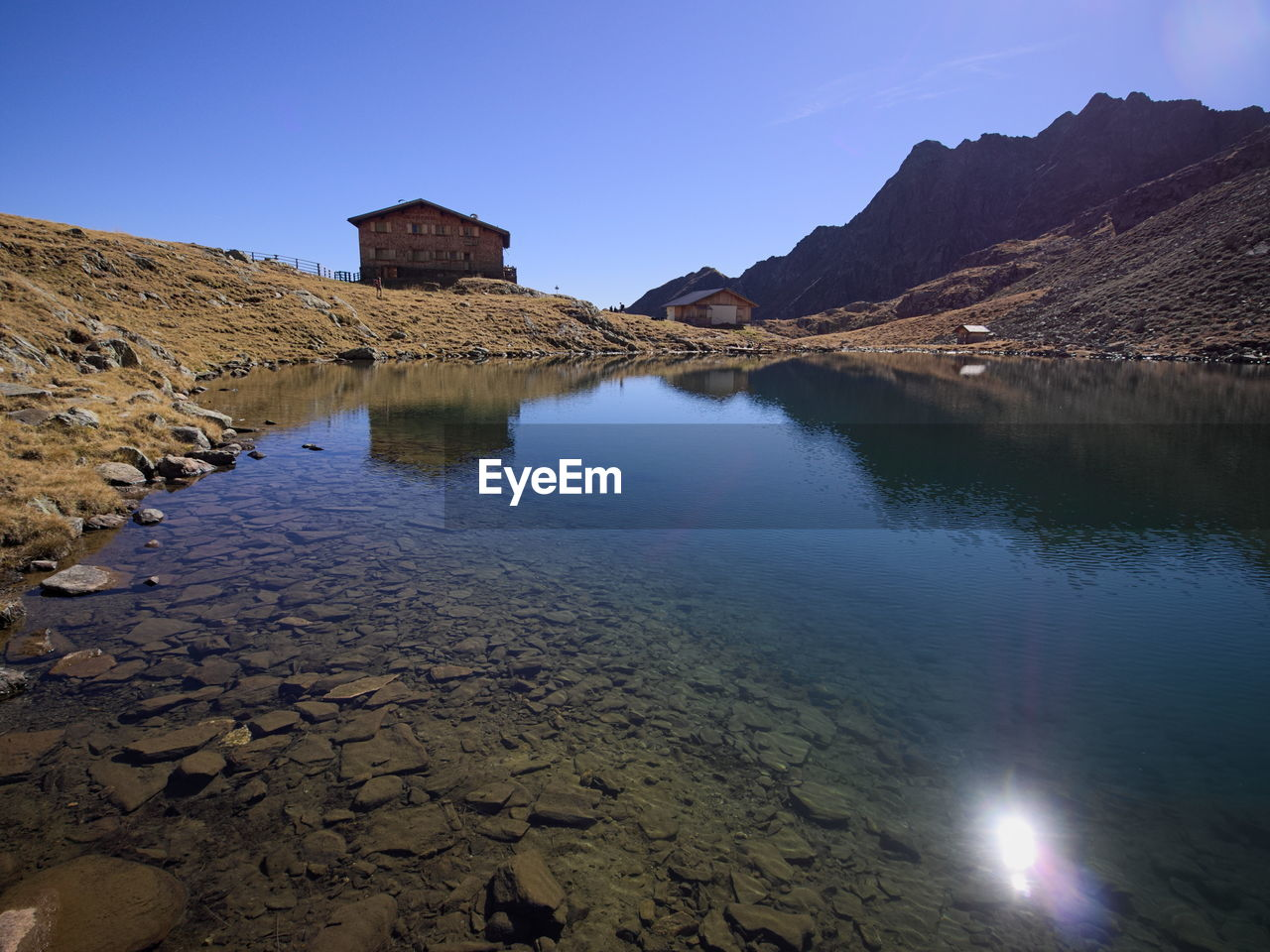 water, sky, tranquility, nature, tranquil scene, mountain, beauty in nature, clear sky, scenics - nature, no people, reflection, lake, rock, day, architecture, solid, built structure, rock - object, non-urban scene, outdoors, arid climate