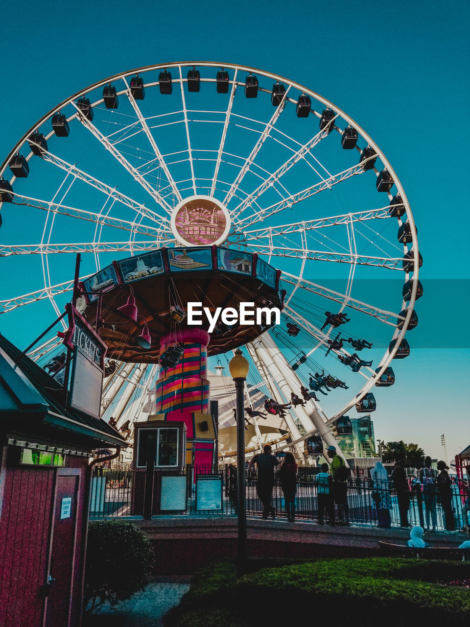 amusement park, arts culture and entertainment, amusement park ride, sky, ferris wheel, built structure, architecture, leisure activity, nature, day, clear sky, low angle view, group of people, real people, outdoors, blue, shape, spinning, carnival, large group of people, fairground