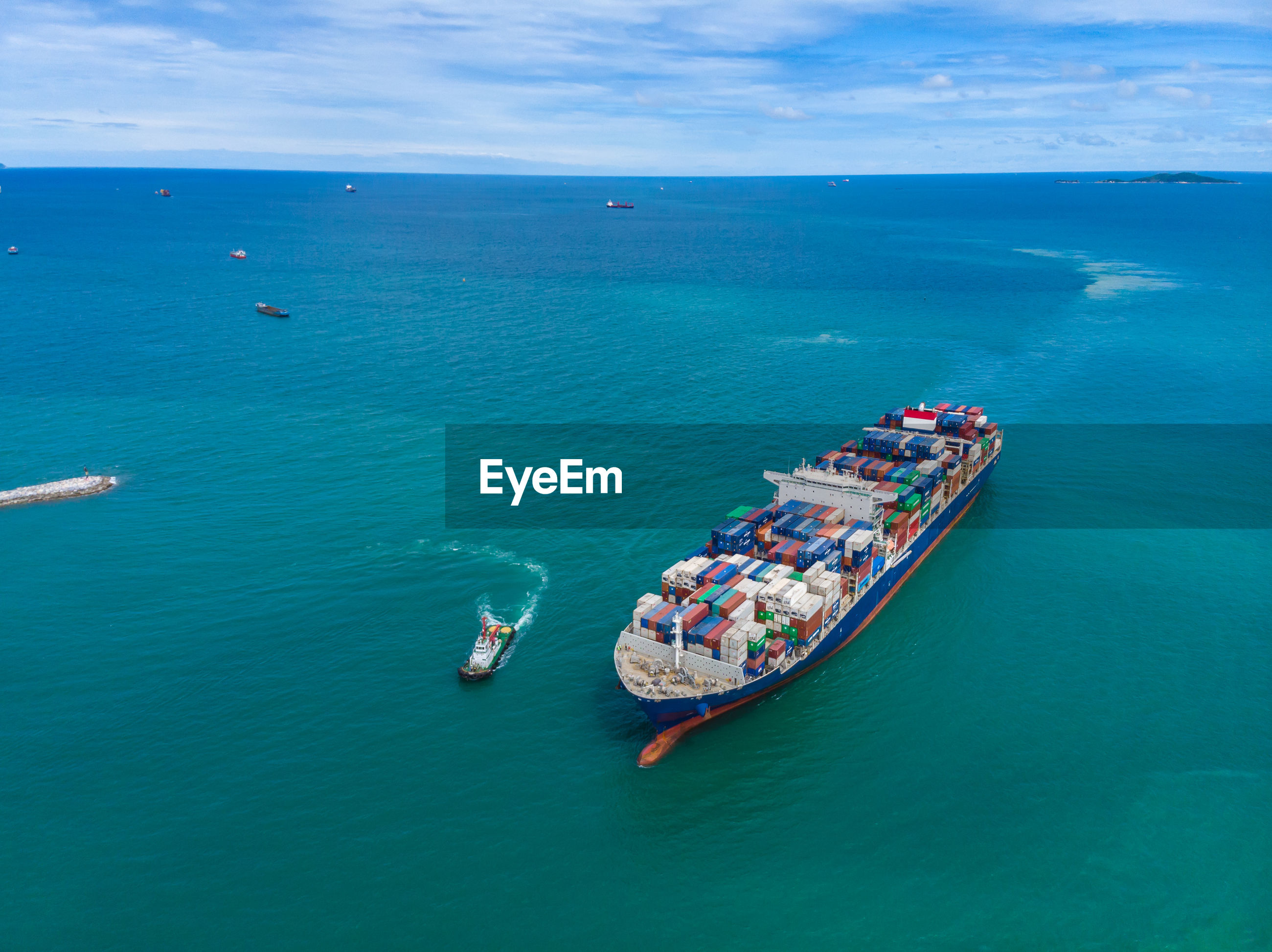 High angle view shipping containers sailing on the green sea