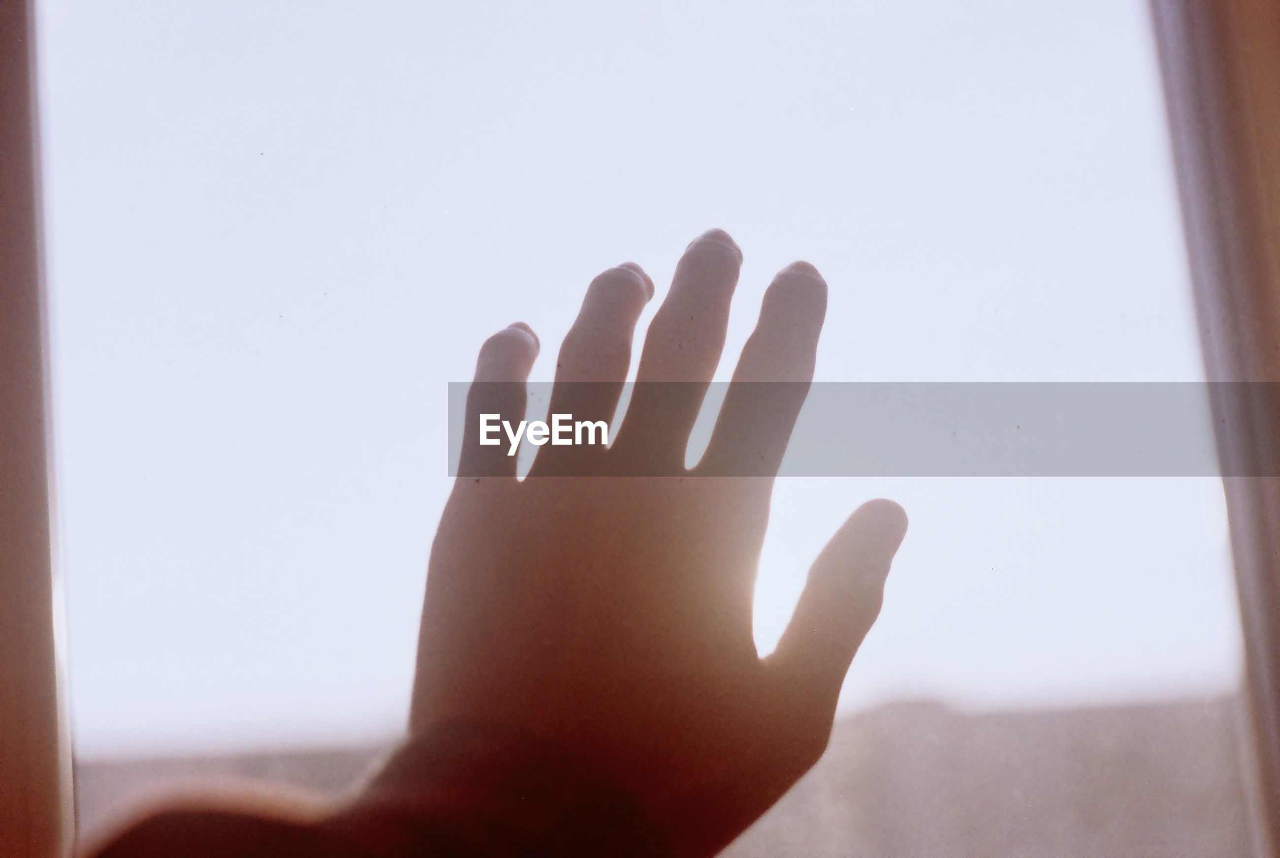 Close-up of hand touching window against sky