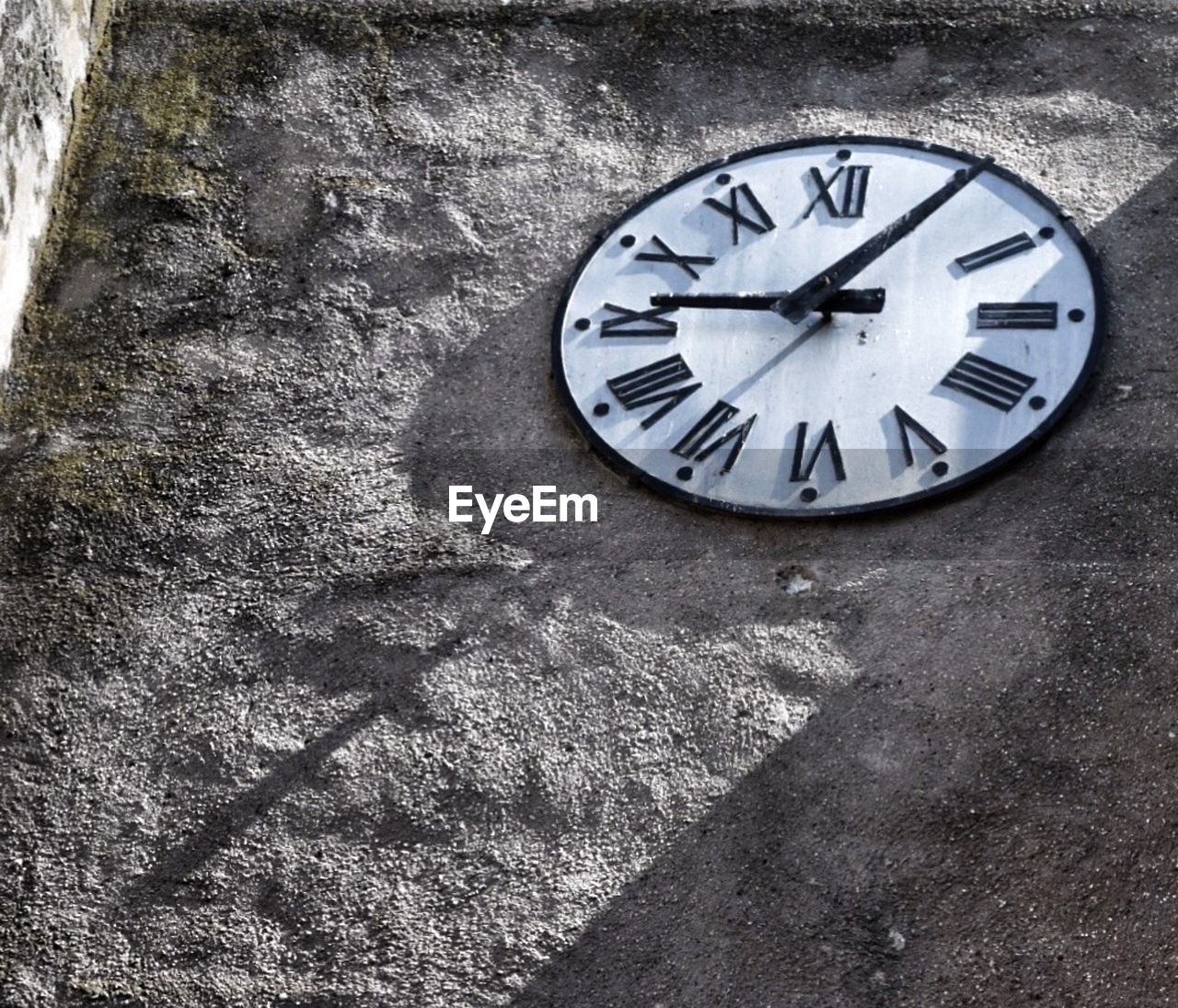 Low Angle View Of Clock Against Wall
