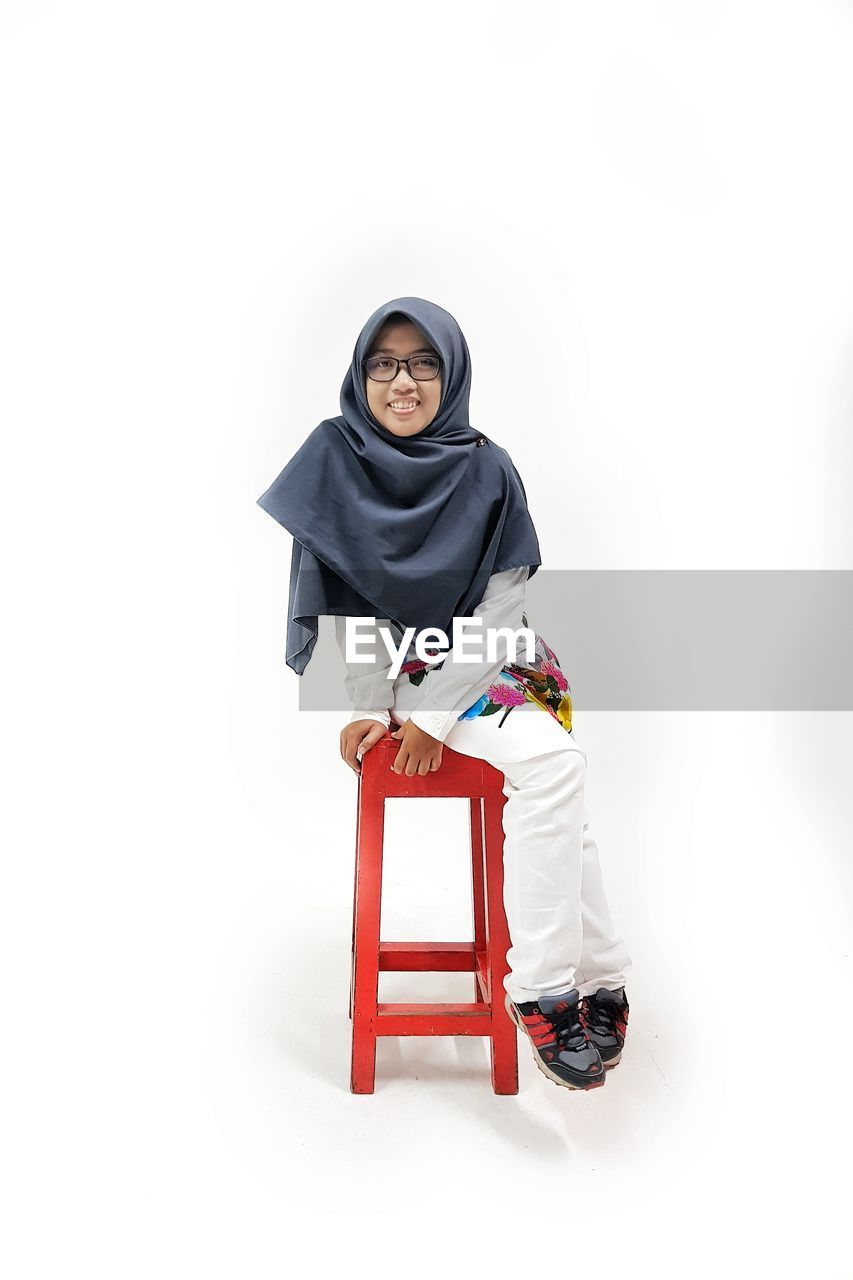 Portrait of smiling young woman wearing hijab sitting on stool against white background