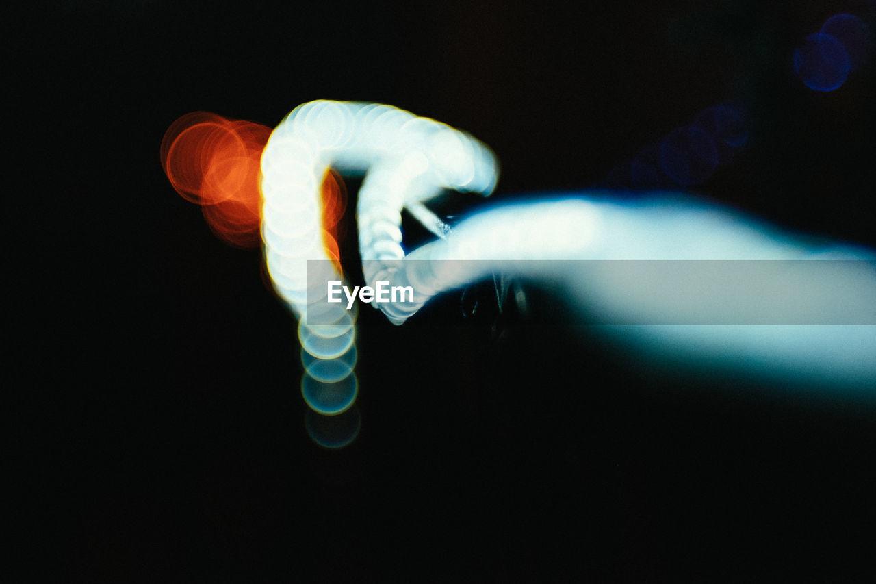 studio shot, human body part, human hand, illuminated, black background, one person, indoors, close-up, night, people