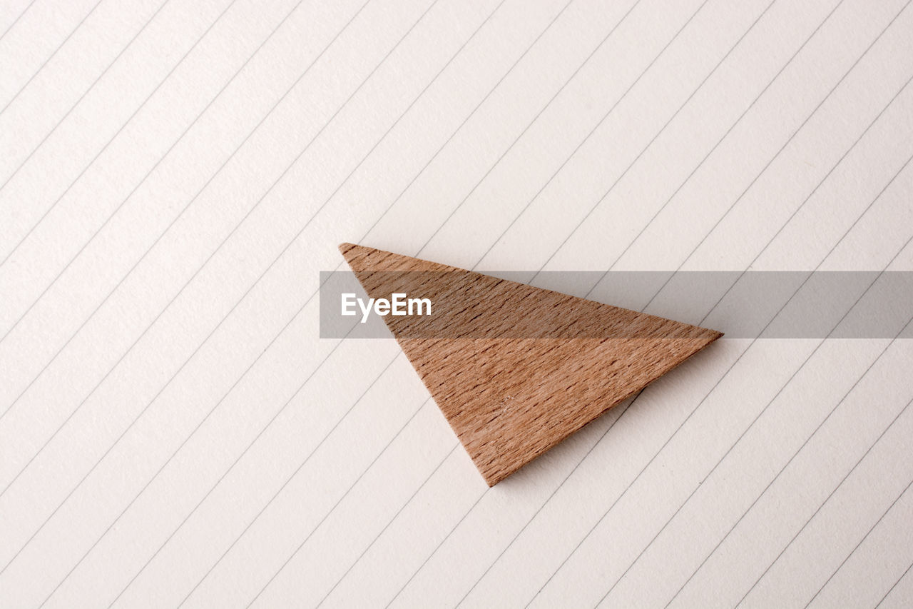 indoors, wood - material, still life, no people, paper, close-up, high angle view, studio shot, brown, creativity, pattern, copy space, shape, art and craft, simplicity, white background, table, single object, pencil, blank