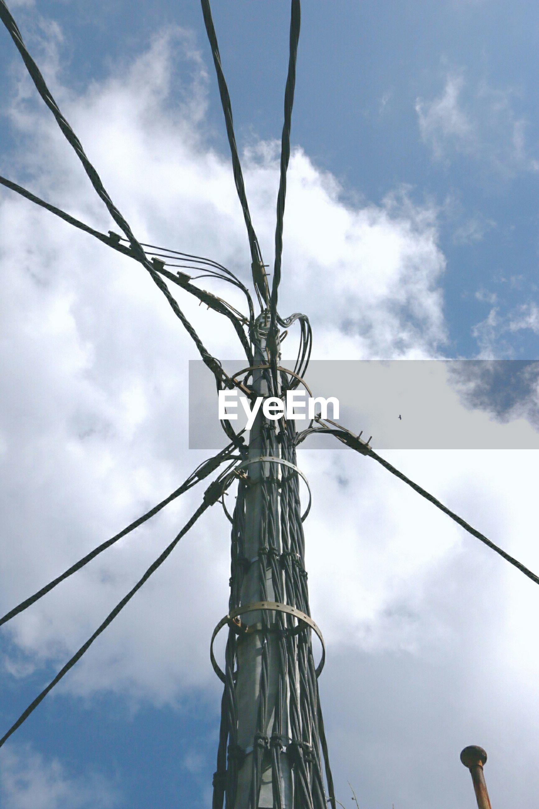 Low angle view of electricity pylon against cloudy sky