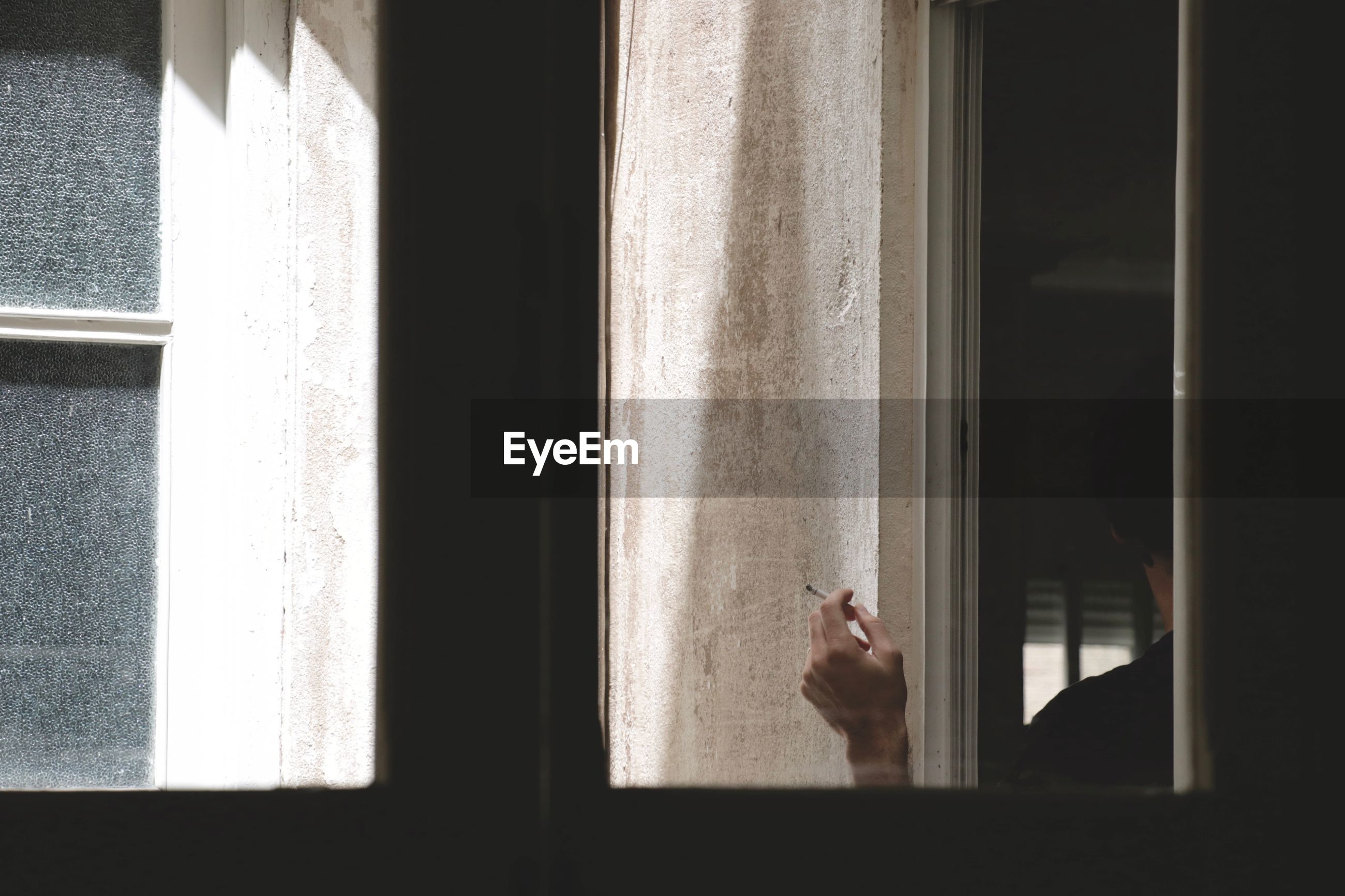 Cropped image of man holding cigarette seen through glass window